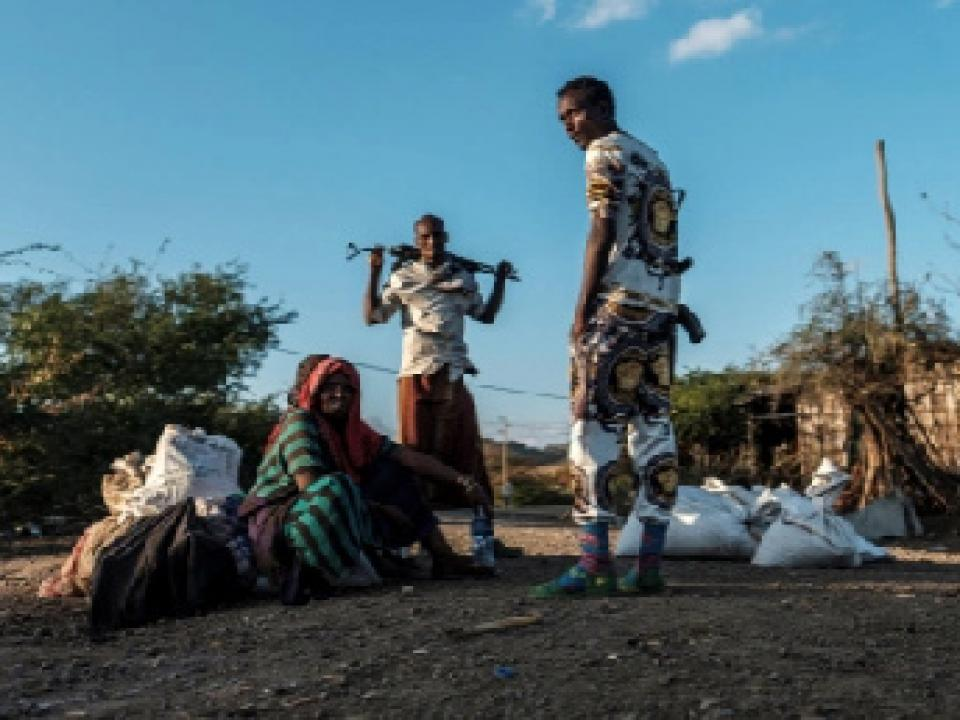 Men holding weapons stand next to a woman in the village of Bisober, in Ethiopia's Tigray region