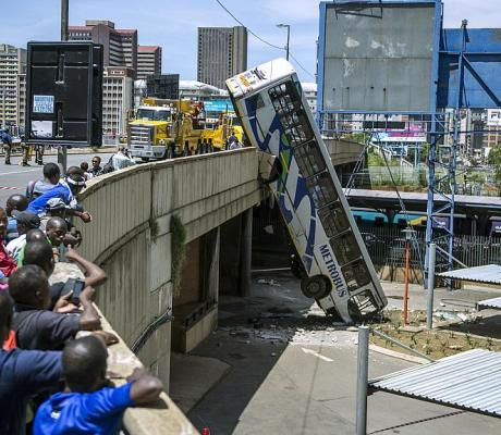 Onlookers gather on Queen Elizabeth bridge to look at a public transport bus that drove over the side of the bridge in Johannesburg, South Africa, on February 25, 2015